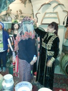Host demonstrating how a headwear for females would be worn.